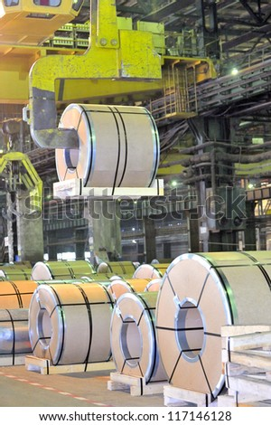 loading of metal on a roll in the plant, steel coils - stock photo