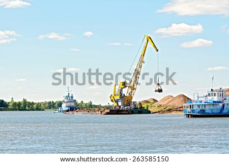 Loading sand with the help of a crane on a barge on the water and sky background of yellow sand. River White, Russia - stock photo
