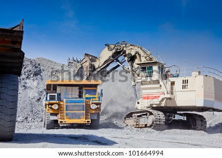Loading the gold ore into heavy dump truck at the opencast mining - stock photo