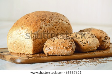 Loaf of bread and rolls on breadboard - stock photo