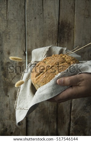 Loaf of Bread in Cloth in Mans Hand on Old Wooden Background