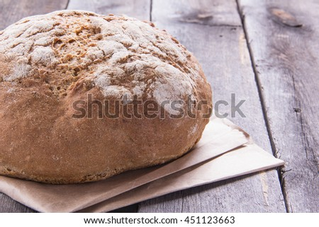 Loaf of bread on an old the wooden table, close-up