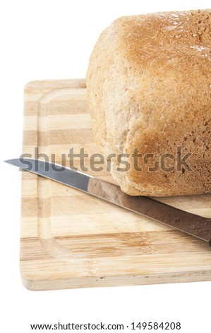 loaf of bread on chopping board with knife