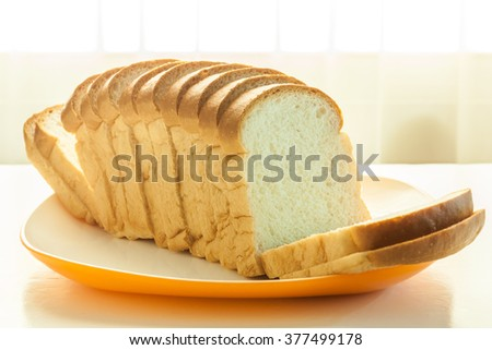 Loaf of bread sliced in a plate on a table near window with sunlight - stock photo