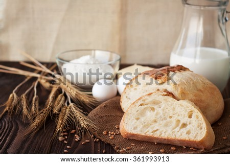 Loaf of bread with ingredients on rustic wooden table