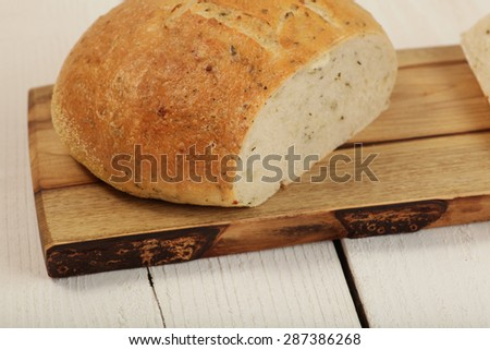Loaf of feta herb bread on a cutting board - stock photo