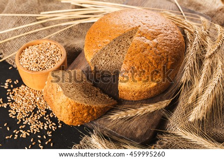 loaf of fresh bread on a wooden board. Ears of wheat - stock photo
