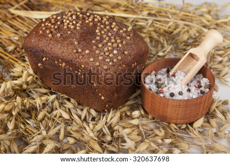 Loaf of homemade bread with black mustard seeds on a table with spikelets of rye and salt shaker of salt. - stock photo