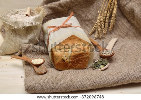 Loaf of homemade whole grain bread with pumpkin, flax, sunflower and sesame seeds on jute cloth with sack of whole grain flour - stock photo