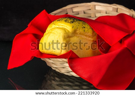 Loaf of Poppy seed bread in basket wrapped in red cloth reflecting in glass tabletop.  Kitchen Art Still Life - stock photo