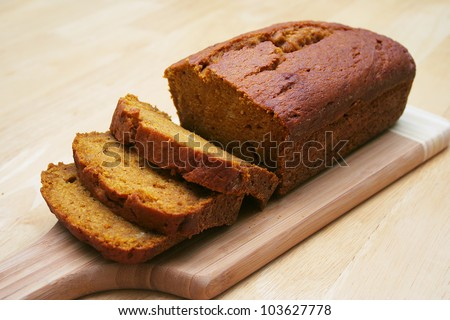 Loaf of Pumpkin Bread Sliced on a Cutting Board - stock photo