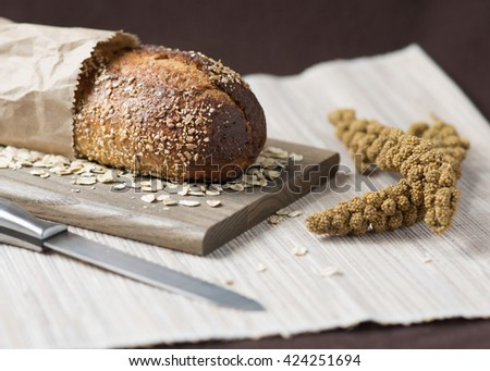 Loaf of rustic whole grain bread in paper bag with knife and millet spray on woven cloth with dark brown background. - stock photo
