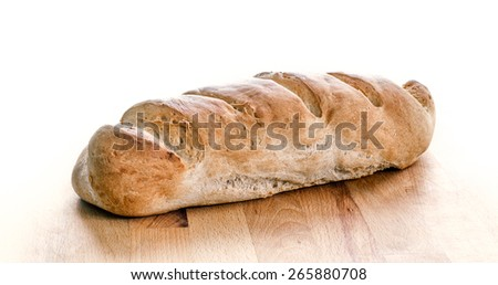 Loaf of whole wheat bread isolated on white. Home made organic crunchy tasty healthy bread sitting on a wooden surface - cutting board is back lit - stock photo