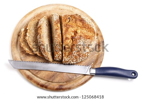 Loaf of wholemeal bread with first half already cut into slices. Top view. - stock photo