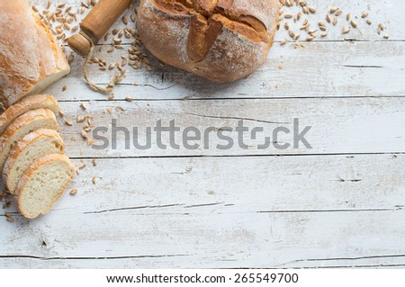 Loafs of bread and rolling pin on rustic table with grain - stock photo