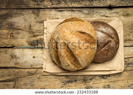 Loafs of different species of bread on wood background with paper bag. Top view - stock photo