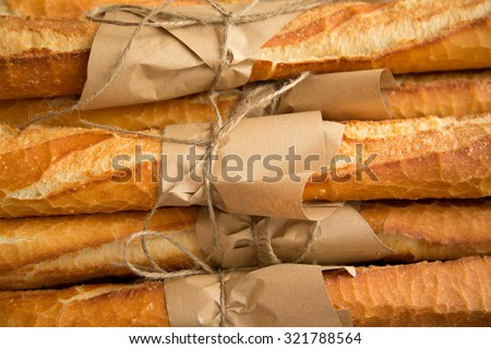 Loafs of French baguette bread tied together with paper and string - stock photo