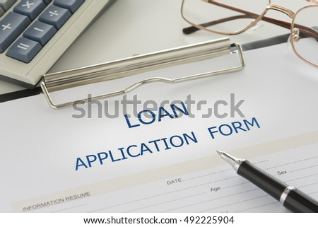 Loan agreement form on desk with calculator in bank. top view. view form above.