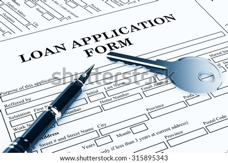 Loan Application Form with House Key and pen on the table