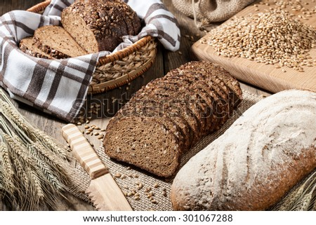 Loaves of rye bread, rye ears, barley grain and bread knife on the  wooden table - stock photo