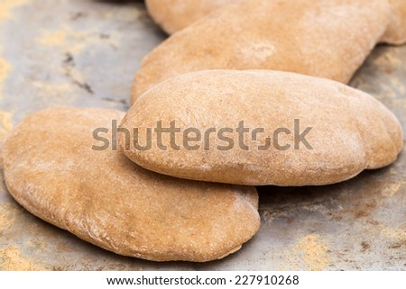 Loaves of traditional Egyptian homemade brown pita bread, fresh from the oven. called aish baladi - stock photo