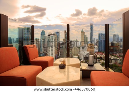 Lobby area of a hotel which can see cityscape at sunset, comfortable sofa unit in front of panoramic view windows overlooking the cityscape with outdoor patio - stock photo