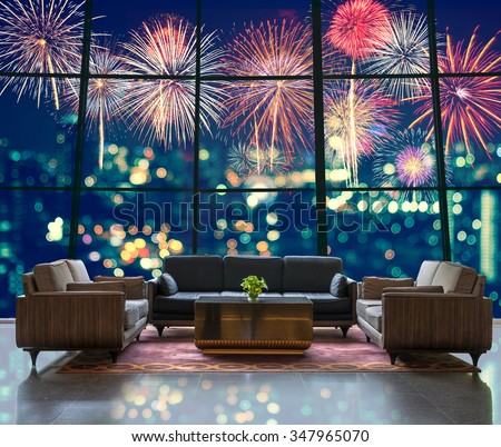Lobby area of a hotel which can see Fantastic festive new years colorful fireworks on cityscape blurred photo bokeh in celebration night - stock photo