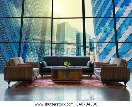 Lobby area of a hotel which can see Modern business building glass of skyscrapers with sun - stock photo
