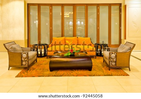 Lobby interior of a hotel with sofa, armchairs and coffee table - stock photo