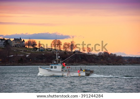 Lobster boat returns to Portland, Maine harbor at sunset - stock photo