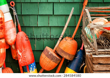 Lobster buoys and traps hanging on a green wood shingled wall. Colorful image with copy space. Horizontal - stock photo