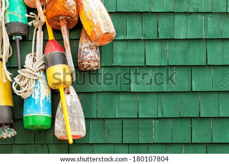 Lobster buoys hanging on a green wood shingled wall. Copy space. - stock photo