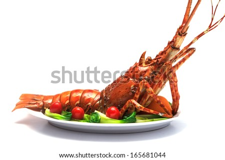 Lobster served with vegetables and tomato on white plate. - stock photo
