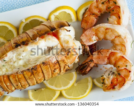 Lobster tail and jumbo shrimps with lemon and butter. - stock photo
