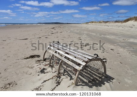Lobster trap on a deserted beach - stock photo