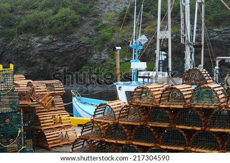 Lobster traps, boats and other fishing equipment in the nautical setting - stock photo