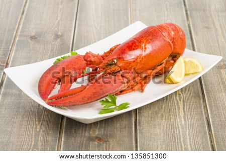 Lobster with lemon wedges. - stock photo