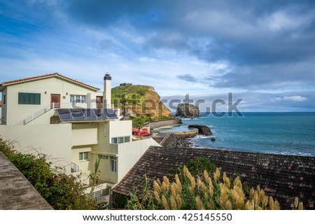 Local houses, ocean view with dramatic sky and old fortress ruins on the steep rock. Typical Madeira island landscape in Porto da Cruz. - stock photo