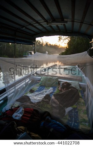 Local 'klotok' boat on Sekonyer River into Tanjung Puting Jungle, Borneo, Indonesia: sleeping on the boat   - stock photo