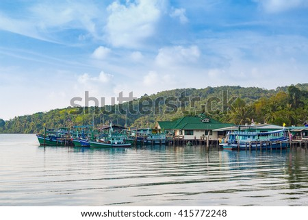 Local material traveling with home stands into sea / fishing village seascape in Thailand/boats parking at bay/beautiful mountain view