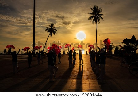 Local people exercise in sunrise at Nha Trang beach, Khanh Hoa, Vietnam. Nha Trang is well known for its beaches and destination for international tourists, attracting large numbers of backpackers. - stock photo