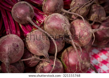 Local produce at a Farmers Market. Bunches of beets on a table ready for sale.