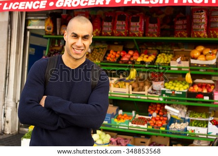 Local trader standing outside his shop - stock photo