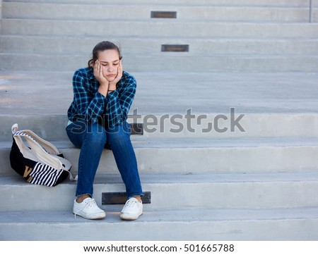 Location shot of a lonely sad teen girl sitting on steps with her backpack
