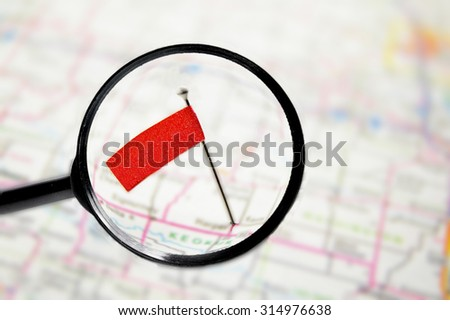 locator pin flag in a map with magnifying glass - stock photo