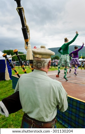 LOCHEARNHEAD, SCOTLAND- JULY, 24,2010: A lone bagpiper plays for dancers doing the sword dance at a Scottish Highland games event on July, 24, 2010 in Lochearnhead.. - stock photo