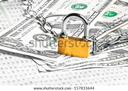 lock security and chain on dollars banknotes on financial newspaper. Money for safety and investment - stock photo