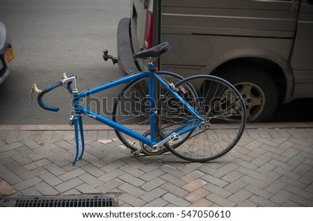 locked blue racing bike with dismounted front wheel to prevent theft