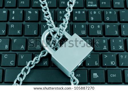 Locked chain on computer keyboard - stock photo