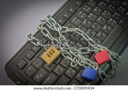 locked chain on computer keyboard as symbol for danger in internet
